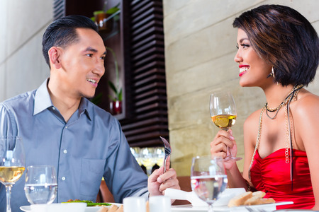 couple dining: Asian couple having dinner and drinking red wine in very fancy restaurant