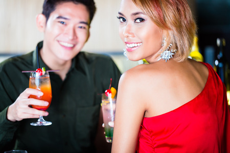 woman bar: Asian couple drinking cocktails in fancy bar Stock Photo