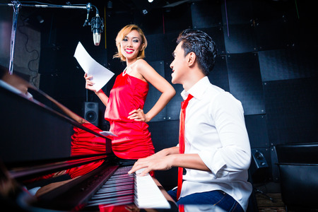 accompaniment: Asian professional singer and pianist working and discussing on new song in studio for composing and recording Stock Photo