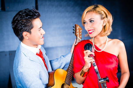 asian produce: Asian professional singer and guitarist recording new song or album CD in studio Stock Photo