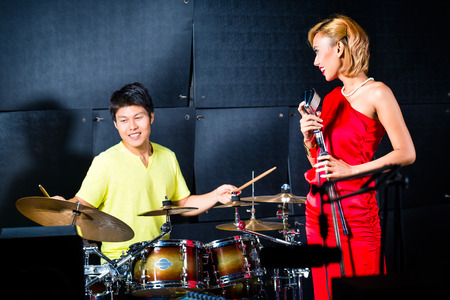 young musician: Asian professional singer and drummer recording new song or album CD in studio
