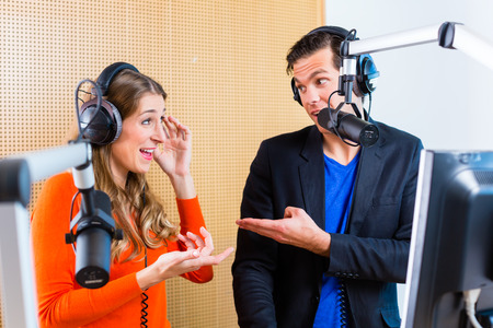 microfono de radio: Los ponentes o moderadores - hombre y mujer - en la estación de radio de hosting espectáculo para la radio en vivo en el estudio Foto de archivo