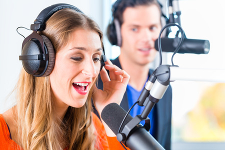 radio station: Presenters or moderators - man and woman - in radio station hosting show for radio live in Studio