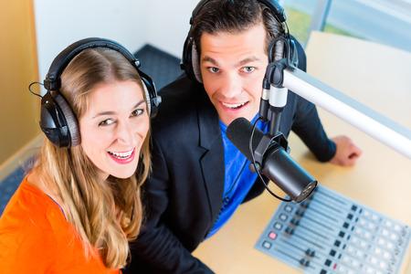 Presentatoren of moderators - man en vrouw - in radiostation hosting-show voor radio wonen in Studio