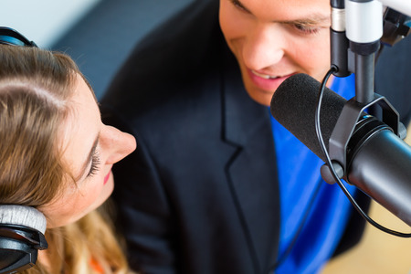 Los ponentes o moderadores - hombre y mujer - en la estación de radio de hosting espectáculo para la radio en vivo en el estudio