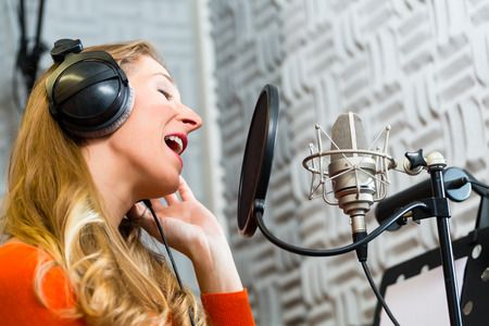 record studio: Young female singer or musician with microphone and headphone for audio recording in the Studio Stock Photo
