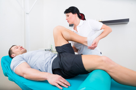 stretches: Patient at the physiotherapy doing physical exercises with his therapist