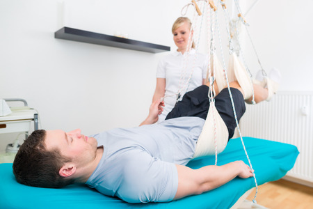 medicate: Patient at physiotherapy doing physical exercises with his therapist in practice on sling table Stock Photo