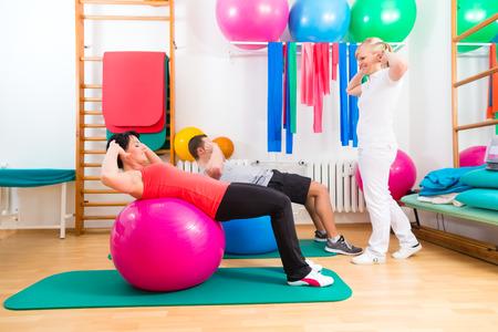 pacientes: Los pacientes con la fisioterapia haciendo ejercicios f�sicos con el terapeuta Foto de archivo