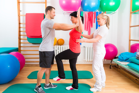 Patients at the physiotherapy doing physical exercises with therapist photo