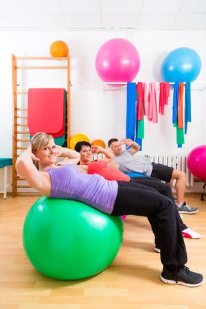 fisioterapia: Los pacientes con la fisioterapia haciendo ejercicios f�sicos con el terapeuta en balones de entrenamiento