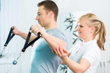 Patiënt bij de fysiotherapie die fysieke oefeningen doet met bowdenkabel