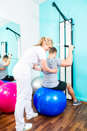 física: Paciente en la fisioterapia haciendo ejercicios físicos con el terapeuta en rehabilitación deportiva Foto de archivo