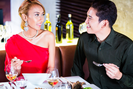 Asian couple fine dining in fancy restaurant Stock Photo