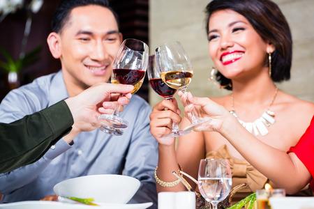 tomando vino: Amigos asi�ticos, dos parejas, comedor en restaurante de lujo de comer buena comida y el vino que bebe
