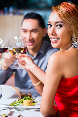 couple dining: Asian friends, two couples, dining in fancy restaurant eating good food and drinking wine
