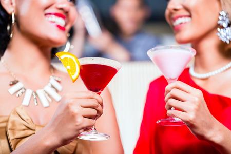 bar: Asian women drinking cocktails in fancy bar