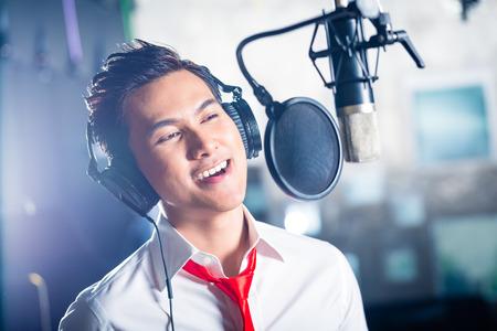 singing: Asian professional musician recording new song or album CD in studio