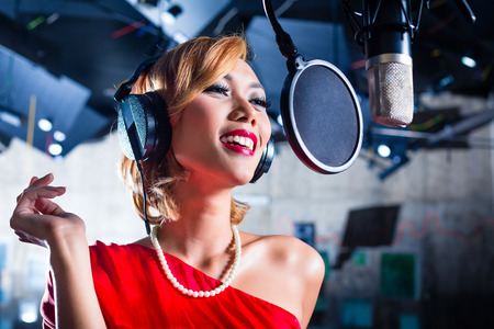 young musician: Asian professional musician recording new song or album CD in studio