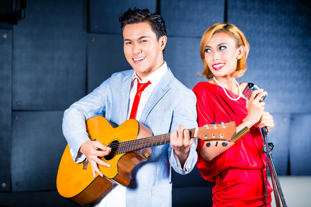 micro recording: Asian professional singer and guitarist recording new song or album CD in studio Stock Photo