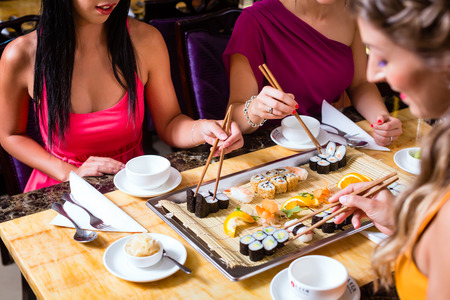sushi chopsticks: Young people eating sushi in Asian restaurant Stock Photo