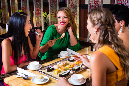 eating dinner: Young people eating sushi in Asian restaurant Stock Photo