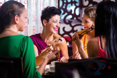 Mladí lidé jíst sushi v asijské restauraci Reklamní fotografie