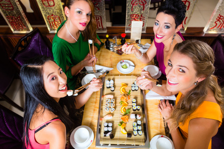 sushi restaurant: Young people eating sushi in Asian restaurant Stock Photo