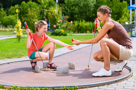 Family playing miniature golf in summer Stockfoto