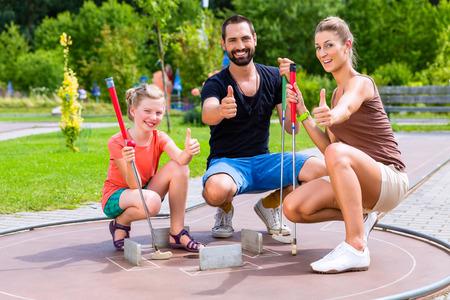 Familie spelen midgetgolf op zomerse dag Stockfoto