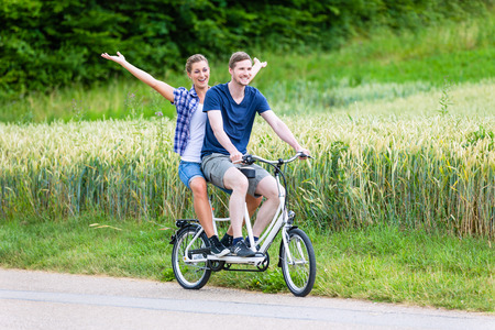 tandem bicycle: Man and woman, a couple,  riding together tandem bike on country lane