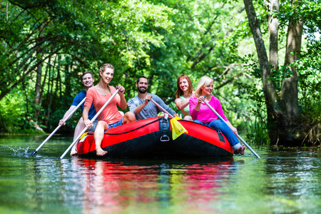Friends paddling on rubber boat at forest river or creek