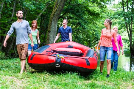 Freunde Durchführung Schlauchboot zum Wald Fluss