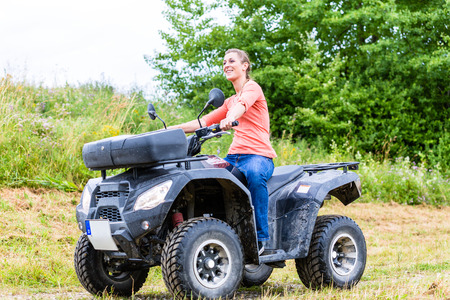 atv: Woman driving off-road with quad bike or ATV