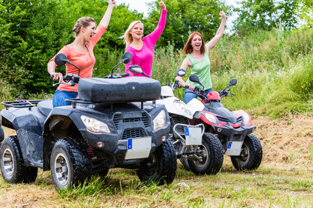 quad: Friends driving off-road with quad bike or ATV Stock Photo