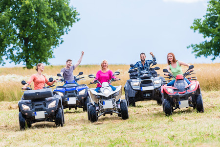 road bike: Friends driving off-road with quad bike or ATV Stock Photo