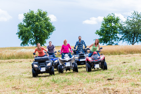atv: Friends driving off-road with quad bike or ATV Stock Photo