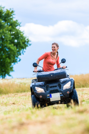 quad: Woman driving off-road with quad bike or ATV