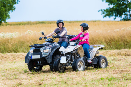 driving: Couple driving off-road with quad bike or ATV
