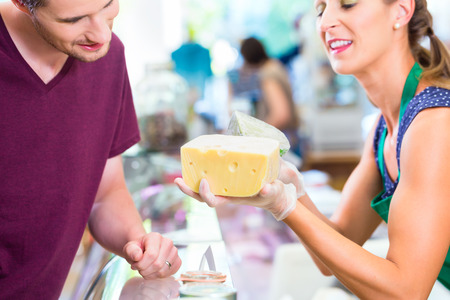 costumer: Saleswoman at organic supermarket counter offering costumer cheese Stock Photo