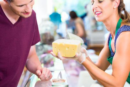 costumer: Saleswoman at organic supermarket counter offering costumer cheese Stock Photo