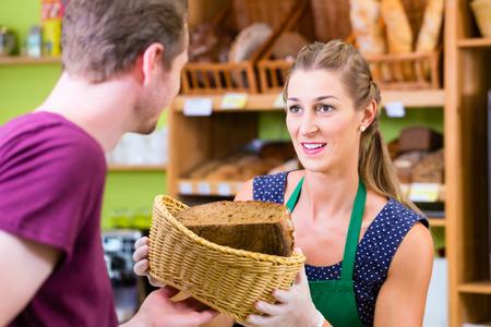 costumer: Female baker at organic supermarket bakery offering costumer bread