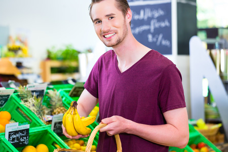 Man selecting bananas while grocery shopping in organic supermarket photo