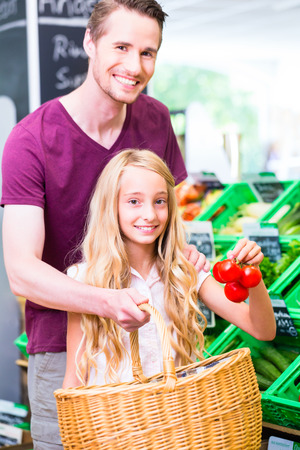 Father and daughter selecting vegetables while grocery shopping in organic supermarket photo