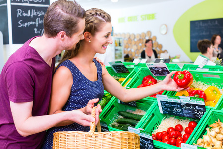 Couple selecting paprika while grocery shopping in organic supermarket photo