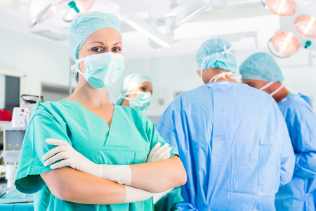 surgical mask woman: Hospital - surgery team in the operating room or Op of a clinic operating on a patient in emergency