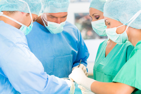 anesthetist: Hospital - surgery team in the operating room or Op of a clinic operating on a patient, perhaps its an emergency a assistant holding a cotton swap forceps