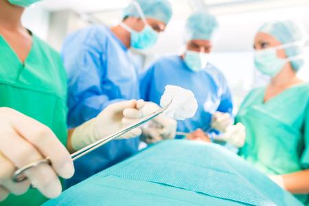 Ziekenhuis - chirurgie team in de operatiekamer of opus van een kliniek die op een patiënt, misschien is het een noodgeval een assistent met een wattenstaafje tang Stockfoto