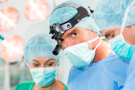 lady with the lamp: Hospital - surgery team in the operating room or Op of clinic operating on patient in an emergency situation