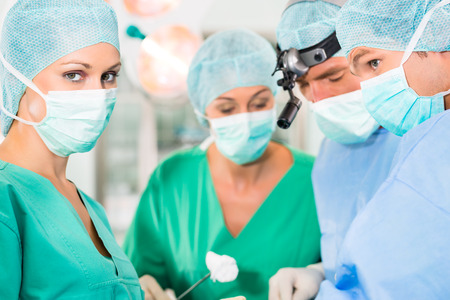 anesthetist: Hospital - doctor surgery team in the operating room or theater of clinic operating on patient, perhaps it is an emergency, assistant holding a cotton swap forceps Stock Photo